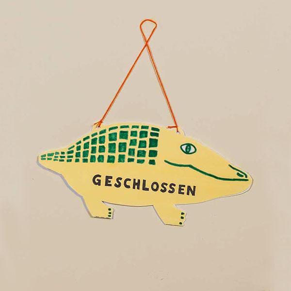 """Stilisiertes Krokodil aus Pappe als Ladenschild zum Wenden, beschriftet mit """"offen"""" und """"geschlossen"""""""