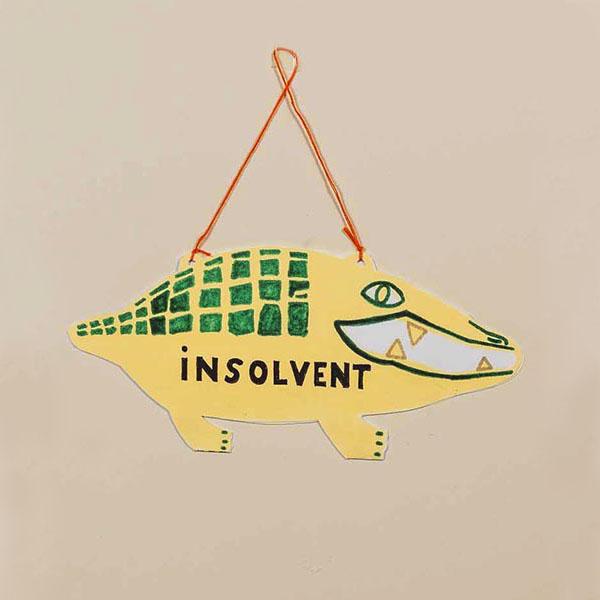 """Stilisiertes Krokodil aus Pappe als Ladenschild zum Wenden, beschriftet mit """"offen"""" und """"insolvent"""""""